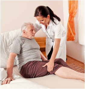 caregiver is helping the old man to stand up