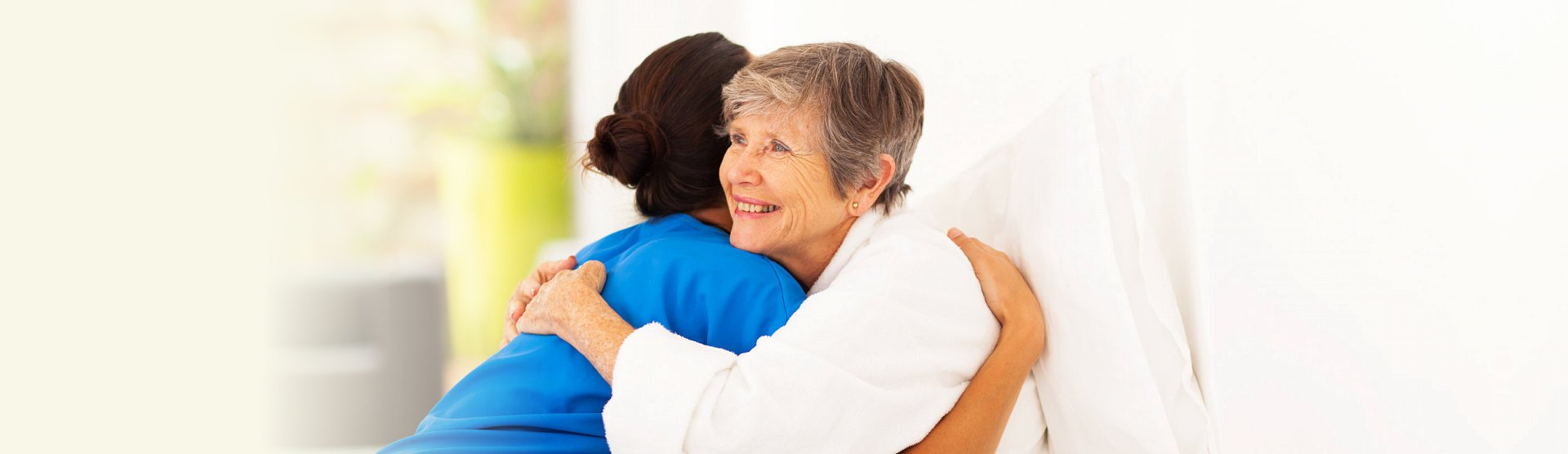 old woman and caregiver are hugging