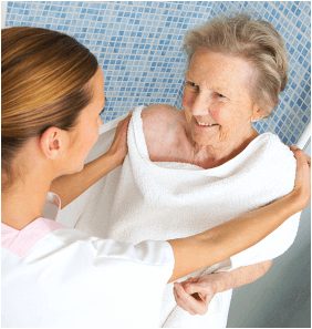 caregiver is helping the old woman in bathing